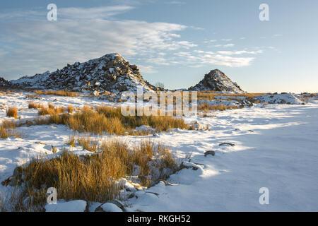 Waste granite piles at Foggintor Quarry in winter Dartmoor national park Devon Uk - Stock Image