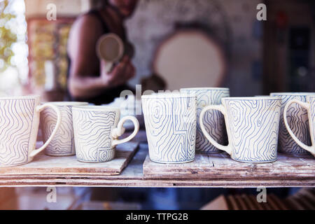 Various clay cups on shelf at workshop - Stock Image