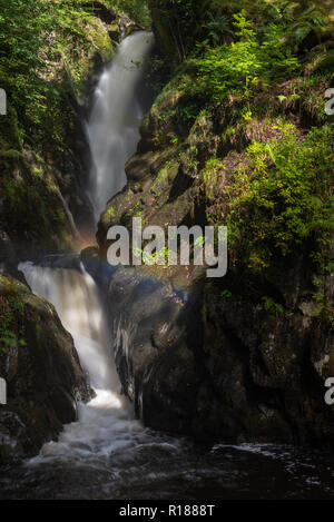 Water drops and sunlight creating a rainbow effect in front of Aira Force, Lake Ullswater, Cumbria, UK - Stock Image