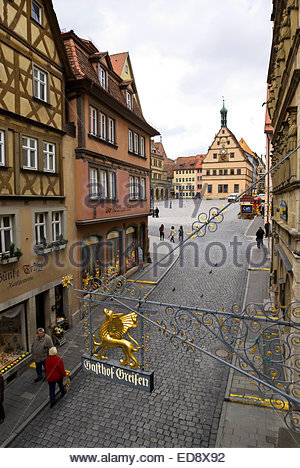 Gasthof Greifen overlooks tourists walking on Obere Schmiedgasse and the Markt in old town section of Rothenburg - Stock Image