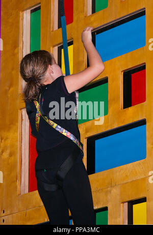 Young Girl Striving To Climb a Climbing Wall Secured By A Safety Harness - Stock Image