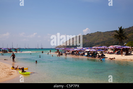 View over beach and bay with tourists on beach and in clear blue water Nai Harn near Cape Promthep. - Stock Image