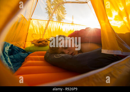 View of a boy sleeping in a tent while on a hiking trip in mountains, Selkirk Mountains, Sandpoint, Idaho, USA - Stock Image