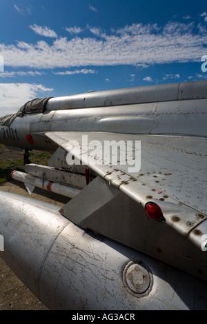 Metal wing with drop tank and AA missile still attached on retired MiG-21 fighter aircraft - Stock Image