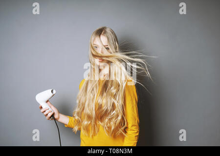 funny young blond woman blow-drying her long hair with blow dryer - Stock Image
