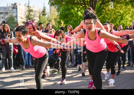 Nis, Serbia - April 20, 2019 Group of woman in pink t shirt practicing Piloxing outside in park on sunny day - Stock Image