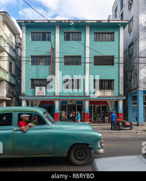 Old Turquoise Cuban / American car driving past a matching colorful Cuban building painted a turquoise color with the pillars painted red. Havana Cuba - Stock Image
