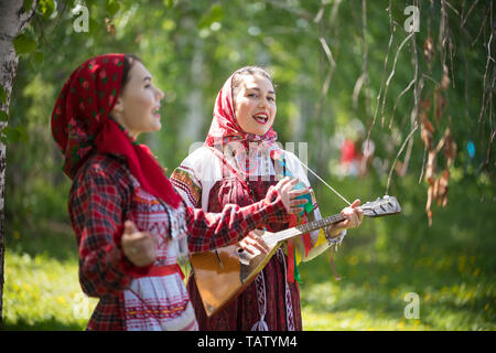 Two young woman in traditional russian clothes singing in the forest. One of them playing balalaika - gorizontal shot - Stock Image