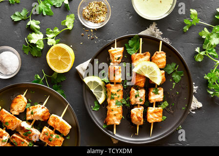 Tasty grilled salmon kebab. Barbecue salmon skewers on black stone background. Top view, flat lay - Stock Image