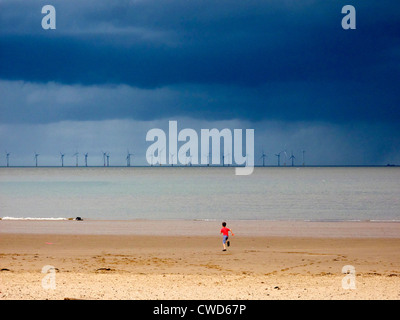 September 2011. Offshore wind farm beyond the beach at New Brighton, Wallasey, Merseyside. A boy runs on beach. - Stock Image