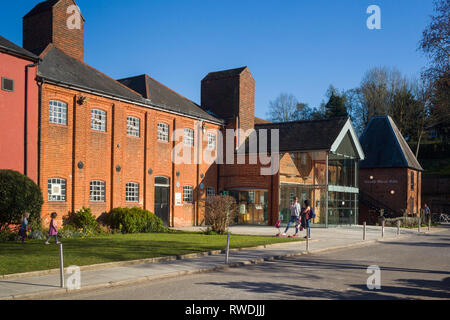 Two young mothers chat in front of he Farnham Maltings, the museum, arts, theatre and community centre in a converted brewery in Farnham, Surrey. - Stock Image