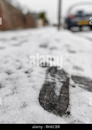 Poole, UK. 1st February 2019. There's snow even in Poole in Dorset, on the south coast of England. Snow in suburbia and footprints on the pavement. Credit: Thomas Faull/Alamy Live News - Stock Image