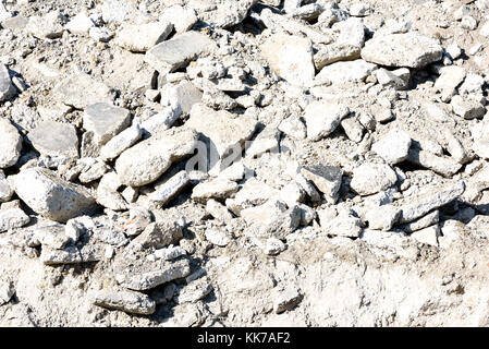 White piles of hardcore rock rubble from broken cement on the ground - Stock Image