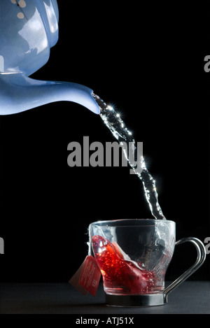 Hot water being poured into a cup with a teabag in it. - Stock Image