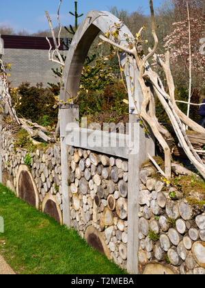 Cut log wall and green oak arch on the front of the Millenium Garden at Buckfast Abbey, Devon, UK - Stock Image