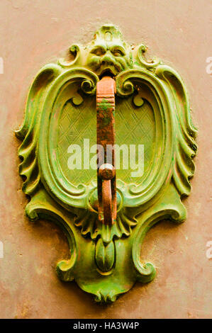 Brass door knocker on a door of a house in Italy - Stock Image