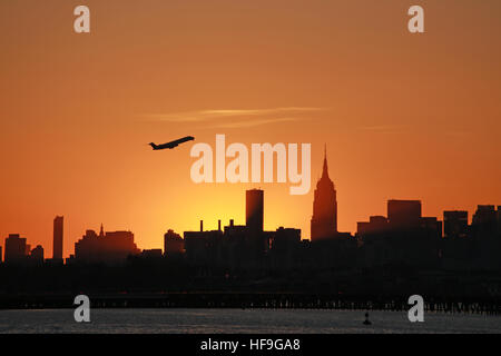 Silhouette of jet taking off over Manhattan skyline, New York, NY, USA - Stock Image
