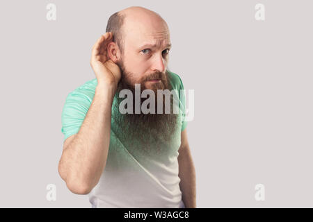 Portrait of attentive middle aged bald man with long beard in t-shirt standing with serious face, holding hand on ear and try to listening or hear. in - Stock Image