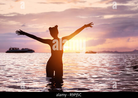 Silhouette of happy slim girl stands in tranquil water with raised arms and greeting sunset - Stock Image