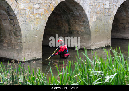 A member of Wiltshire search and rescue volunteers uses a pole to search the river at Bradford on Avon for a possible missing person - Stock Image