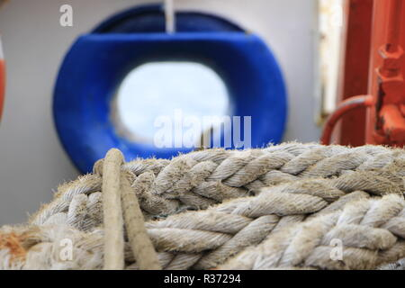 A shot of a rope with a blue ship window on the background - Stock Image