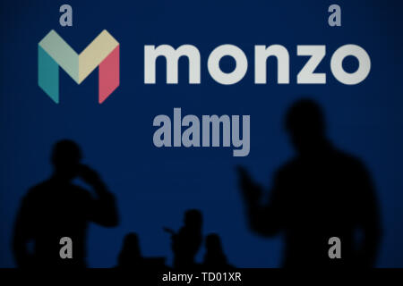 The Monzo bank logo is seen on an LED screen in the background while a silhouetted person uses a smartphone in the foreground (Editorial use only) - Stock Image