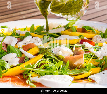Summer food: salad meal served outdoors with mango slices, rocket and parma ham on a white plate with basil dressing poured over - Stock Image