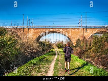 man jogging urban park bridge railway path trail in the city background . - Stock Image