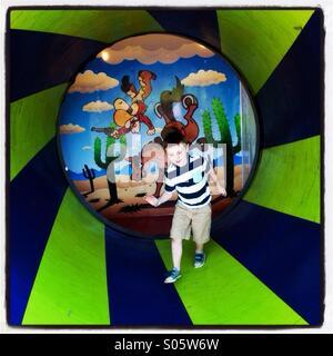 Boy runs through funhouse at a carnival. - Stock Image