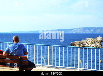 A young man traveler sitting on a bench on the Mediterranean coast on the promenade of Marseille. Back view of the beautiful sea panorama and sailboat - Stock Image