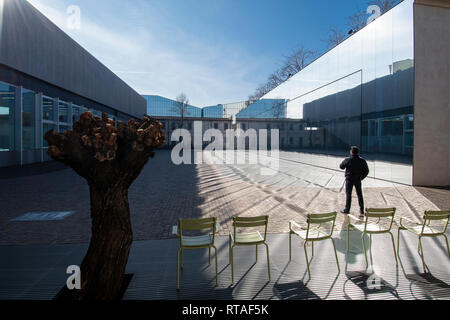 Man standing in one of the courtyards of Fondazione Prada, exterior, Milan, Italy - Stock Image