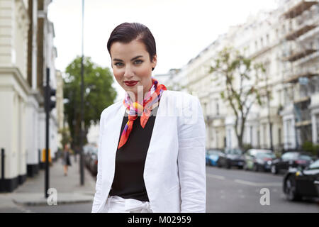 Woman in white linen suit looking to camera in street - Stock Image
