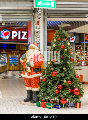 ALLUM, PARTILLE, SWEDEN - DECEMBER 7 2018: Lifesize Santa Claus figure next to beautifully decorated Christmas tree indoors at popular Allum shopping centre or mall just outside Gothenburg, Sweden - Stock Image