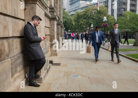 Smart dressed business man using mobile phone in central Birmingham UK - Stock Image