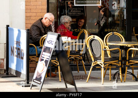 Two elderly women sitting together inside the Cafe Nero deciding what coffees to order in Dundee, UK - Stock Image