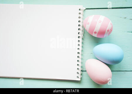 A beautiful and colorful close-up flat of isolated easter eggs in plain colors and striped by a notebook over a pastel blue wooden table with space - Stock Image