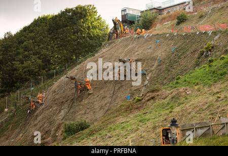 Engineers in harnesses fixed by long cables work on a cliff face at Scarborough - Stock Image