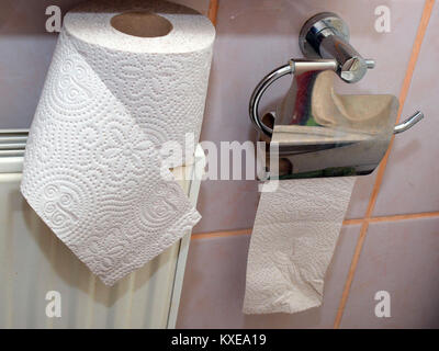 Empty toilet paper roll in holder on tiled wall and full one for replace - Stock Image