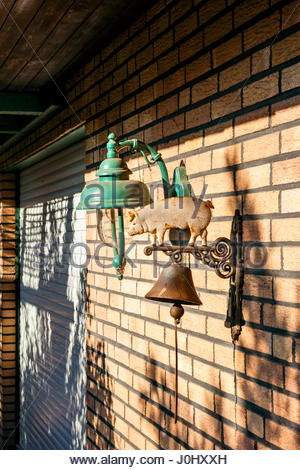 Dinner bell with a pig on top fastened to a brick wall, alongside a lamp - Stock Image