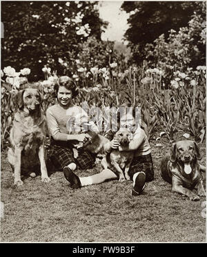 Princess Elizabeth the future Queen Elizebeth II and her sister Princess Margaret in posing with their pet dogs in the grounds of Windsor castle photographed in 1937 - Stock Image