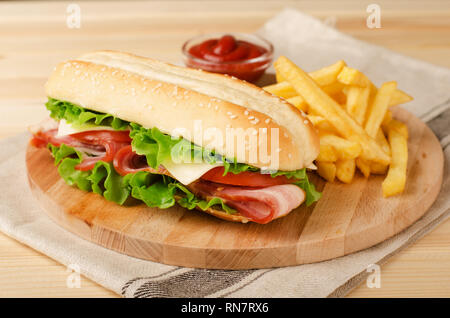Fresh submarine sandwich with ham, cheese, bacon, tomatoes and  lettuce on wooden cutting board with french fries and sauce - Stock Image