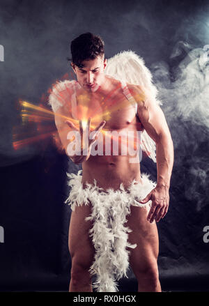 Male angel with white wings in studio shot - Stock Image