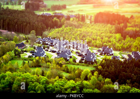 White houses with black roofs in a small forest seen from above - Stock Image