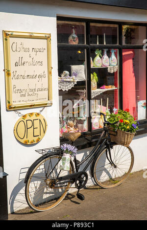 UK, Northern Ireland, Co Antrim, Carrickfergus, Lancasterian Street, bicycle advertising Misha's Country Workshop haberdashery and textile crafts shop - Stock Image