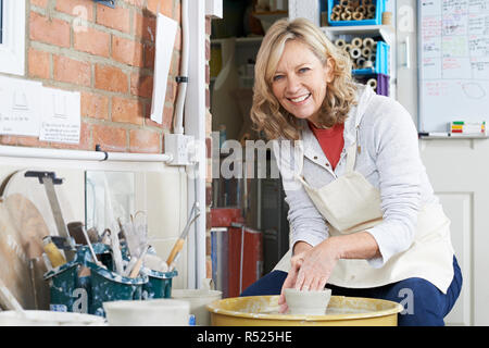 Portrait Of Mature Woman Working At Potters Wheel In Studio - Stock Image