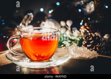 Bright shining cup of hot tea in dark room. Spending winter evening at home - Stock Image
