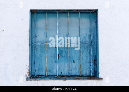 Blue barred square window against a white wall - Stock Image