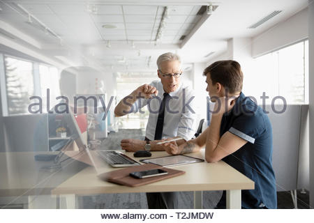 Businessmen talking, planning at computer in office - Stock Image