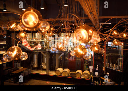 Amsterdam Brewhouse brewery tanks and beer barrels through lights above bar a Toronto Harbourfront restaurant - Stock Image