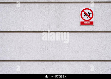 playing football forbidden text and pictogram in Polish on the wall in Warsaw Poland, crack in rough facade - Stock Image